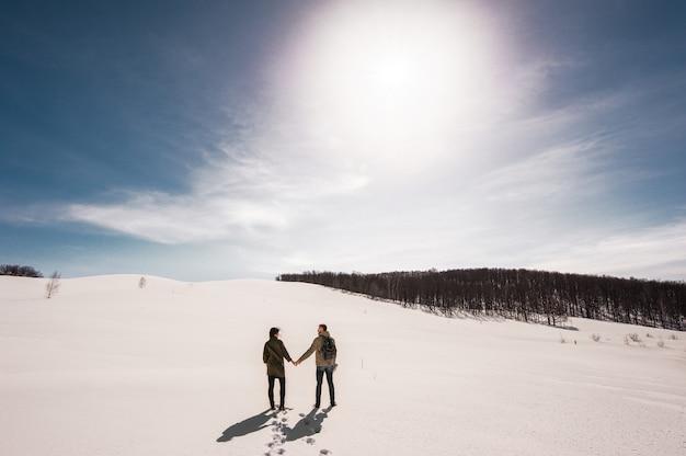 Couple amoureux se promène en hiver dans la neige. homme et femme voyageant. couple amoureux en montagne. voyageurs en montagne. marche d'hiver. aventures d'hiver. marche d'hiver. couple d'amoureux Photo Premium