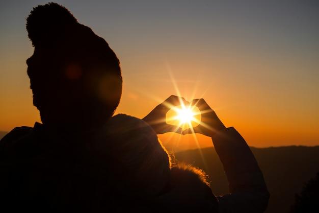 Couple amoureux silhouette rétro-éclairage sur la colline au moment du coucher du soleil Photo gratuit