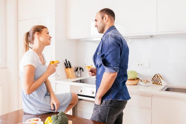 Couple d'amoureux tenant un verre à vin regardant eachother dans la cuisine Photo gratuit