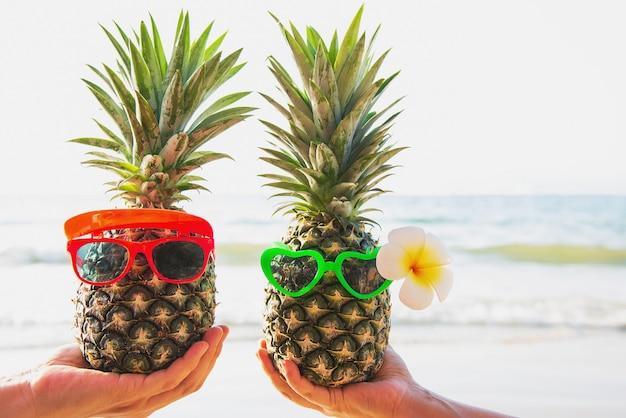 Couple d'ananas frais mettant des lunettes dans les mains d'un touriste avec la vague de la mer - amour heureux et amusement avec le concept de vacances en bonne santé Photo gratuit