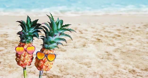 Couple ananas avec des lunettes de soleil sur le sable à la plage Photo Premium