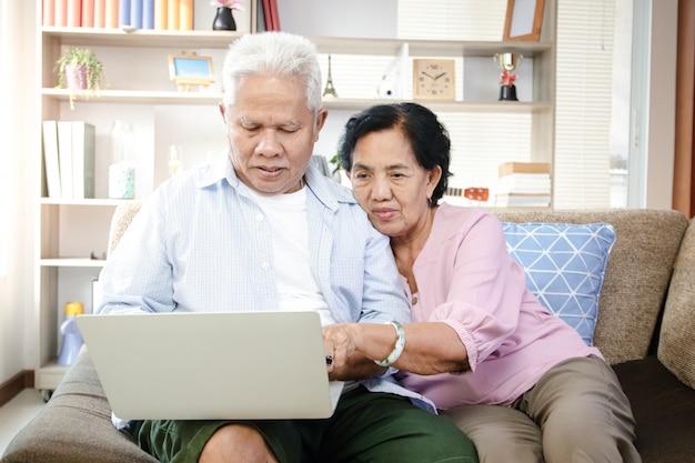 Couple Asiatique âgé Assis Sur Un Canapé Et Utilisant Un Ordinateur Portable Photo Premium