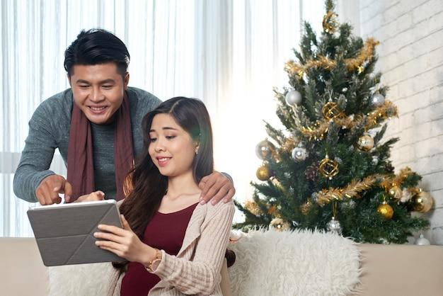 Couple asiatique d'âge moyen en regardant l'écran de la tablette ensemble à la maison à noël Photo gratuit