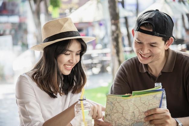 Couple asiatique aime voyager assis au café Photo gratuit