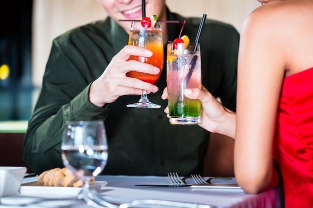 Couple asiatique, boire des cocktails dans un bar chic Photo Premium