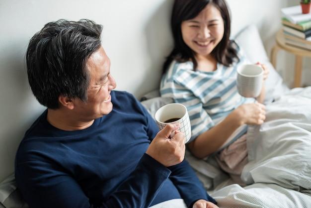 Couple asiatique, boire du café au lit Photo gratuit