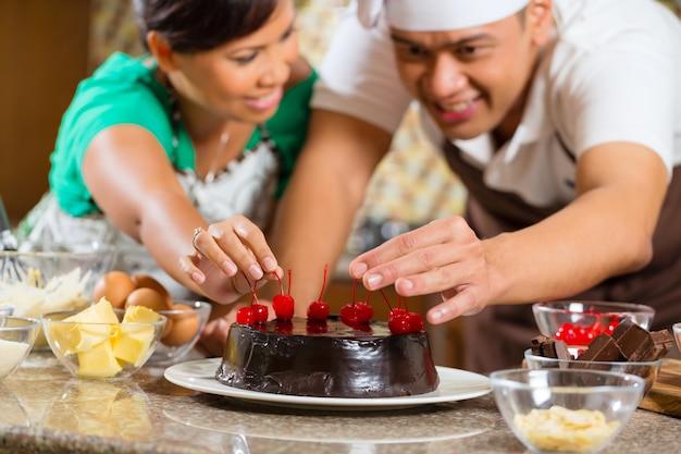 Couple asiatique, cuisson, gâteau chocolat, dans, cuisine Photo Premium