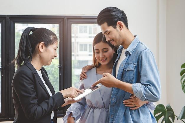 Couple asiatique parlant avec un agent immobilier pour acheter un nouvel appartement.l Photo Premium