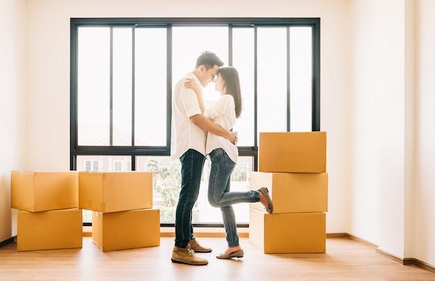 Couple asiatique s'embrassant dans leur nouvelle maison Photo Premium