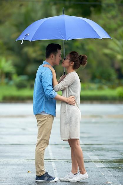 Couple Asiatique S'embrasser Sous La Pluie Photo gratuit