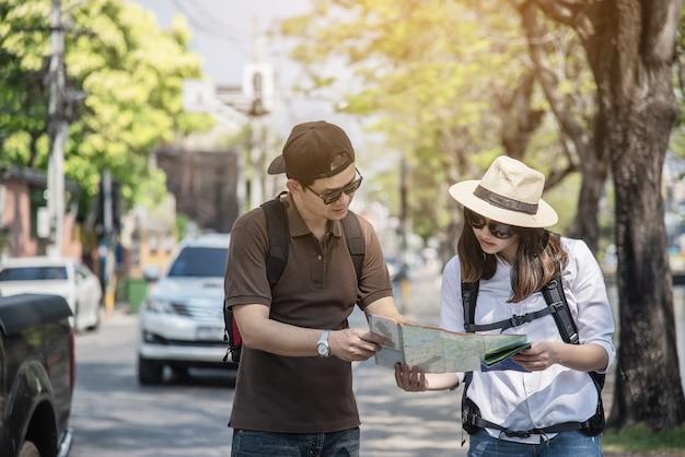 Couple asiatique, touriste, tenue, carte ville, traverser route Photo gratuit