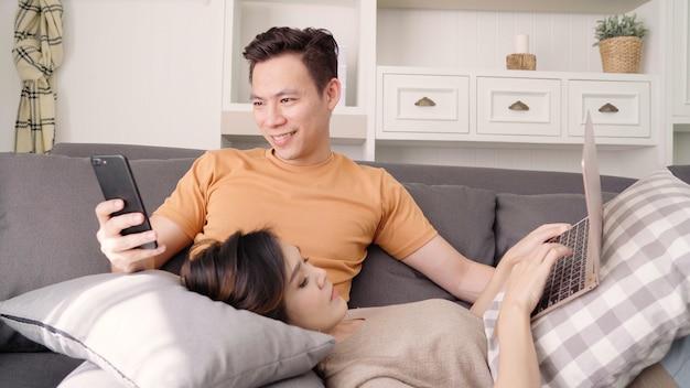 Couple asiatique, utilisation, smartphone, ordinateur portable, vérification, médias sociaux, dans, salon, maison Photo gratuit