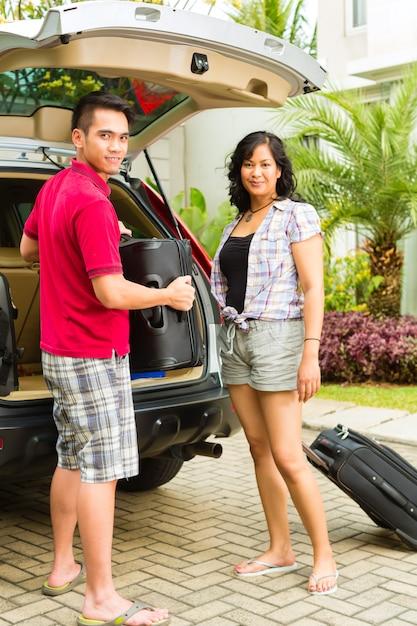 Couple asiatique voiture d'emballage avec des valises pour les vacances Photo Premium