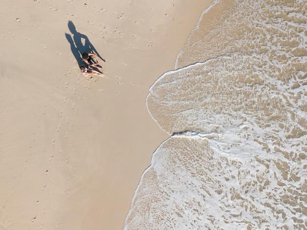 Couple assis au bord de la mer près des vagues de mousse Photo gratuit