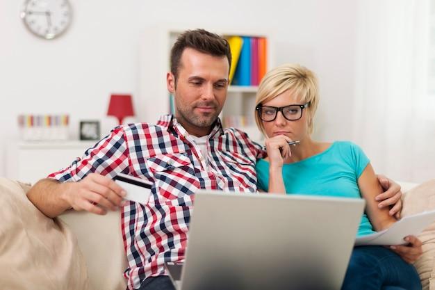 Couple Assis Sur Un Canapé à La Maison Et Payer La Facture En Ligne Photo gratuit