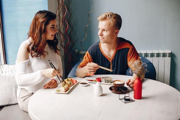 Couple assis dans un café et mangeant des sushis Photo gratuit