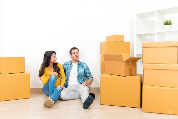 Couple assis ensemble sur le sol après avoir emménagé dans leur nouvelle maison Photo Premium
