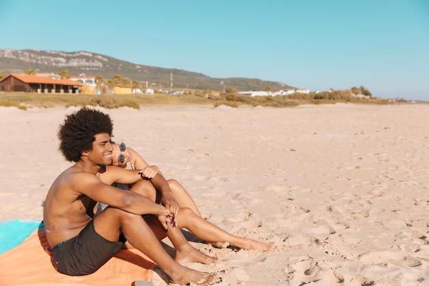 Couple Assis Sur La Plage Photo gratuit