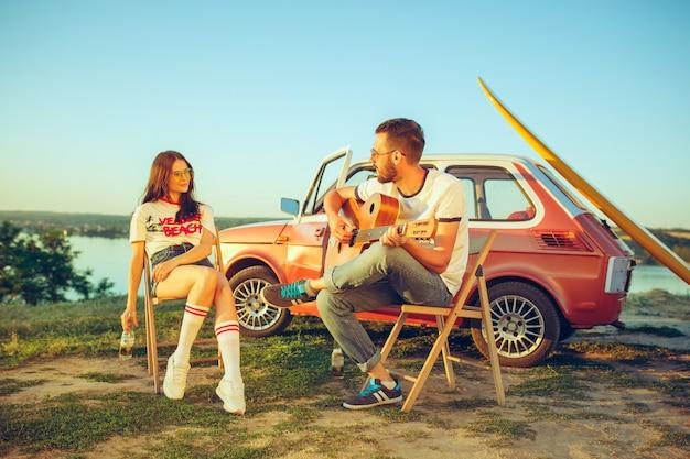 Couple Assis Et Reposant Sur La Plage à Jouer De La Guitare Un Jour D'été Près De La Rivière Photo gratuit
