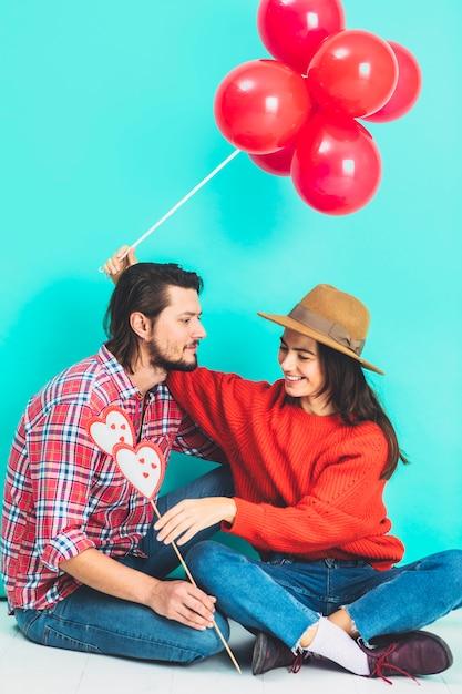 Couple Assis Sur Le Sol Avec Des Ballons Et Des Coeurs Sur Un Bâton Photo gratuit
