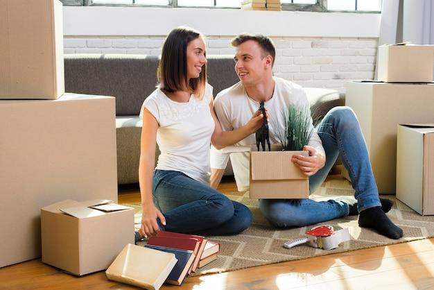 Couple assis sur le sol qui se regardent Photo gratuit