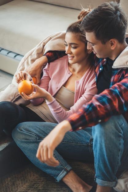 Couple Assis Sur Le Sol Recouvert D'une Couette Et Manger Une Orange S'embrassant Photo Premium