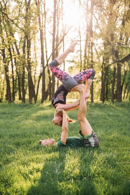 Couple d'athlètes pratiquant le yoga acro sur l'herbe verte Photo gratuit