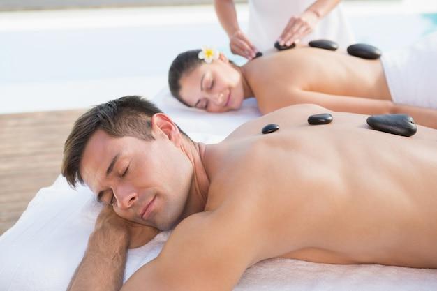 Couple Attrayant Bénéficiant De Massage Aux Pierres Chaudes Au Bord De La Piscine Photo Premium