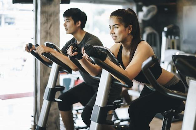 Couple attrayant à cheval sur le vélo de spinning au gymnase. travailler ensemble Photo Premium