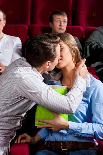 Couple au cinéma avec pop-corn s'embrasser Photo Premium