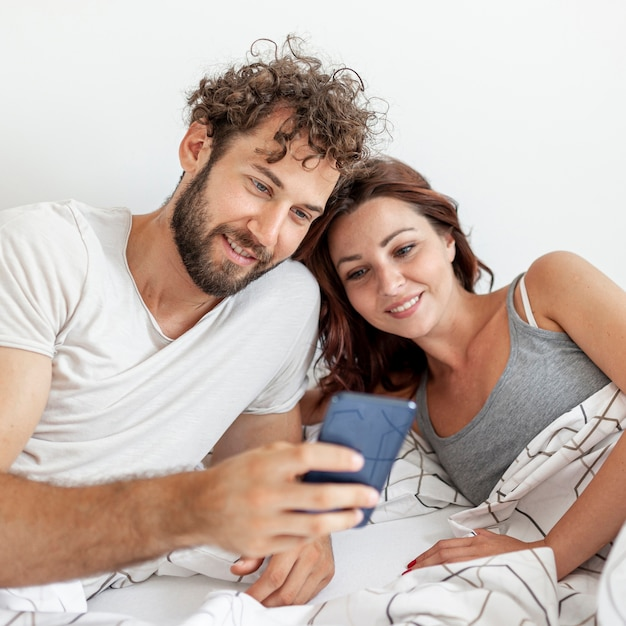 Couple au lit en regardant au smartphone Photo gratuit