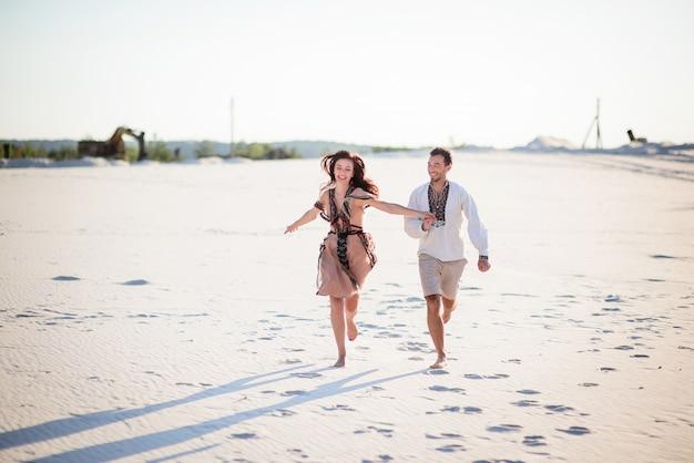 Couple aux pieds nus dans des vêtements brodés brillants s'exécute sur un sable blanc Photo gratuit