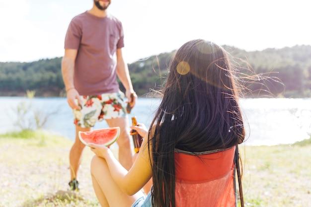 Couple ayant une collation sur la plage Photo gratuit