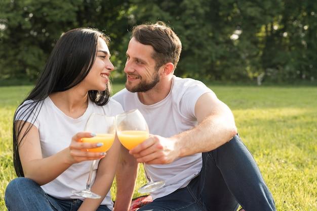 Couple ayant du jus d'orange sur une couverture de pique-nique Photo gratuit