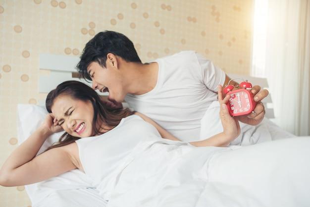 Couple ayant du mal à se lever tôt le matin sur le lit Photo gratuit