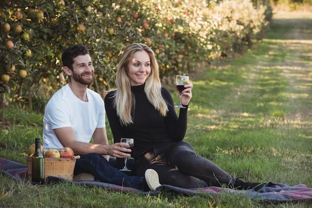 Couple ayant du vin dans un verger de pommiers Photo gratuit