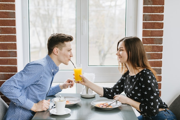 Couple ayant un jus d'orange dans un restaurant Photo gratuit