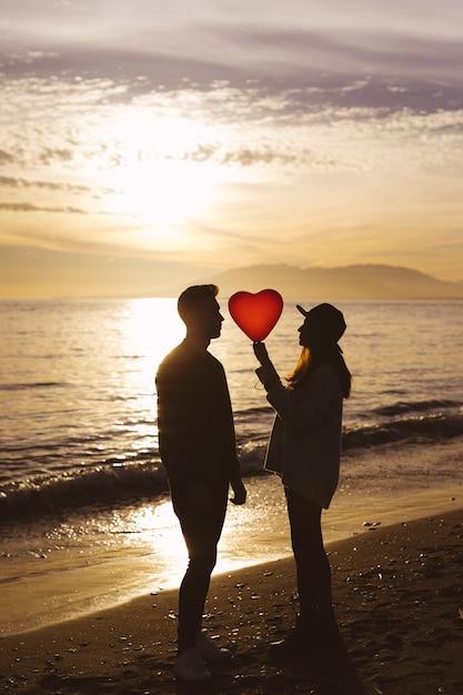 Couple avec ballon coeur au bord de la mer en soirée Photo gratuit