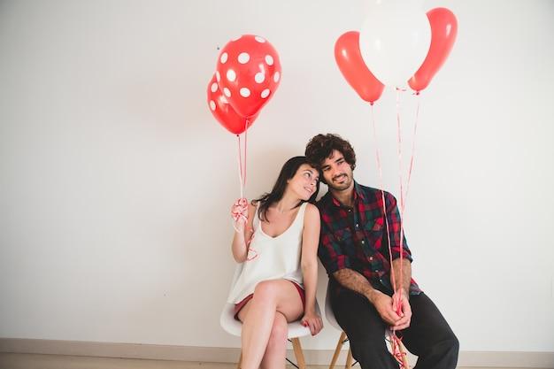 Couple Avec Des Ballons Dans Les Mains Assis Sur Des Chaises Blanches Photo gratuit
