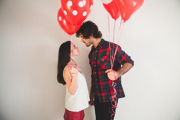 Couple Avec Des Ballons Dans Les Mains En Regardant Les Uns Les Autres Photo gratuit