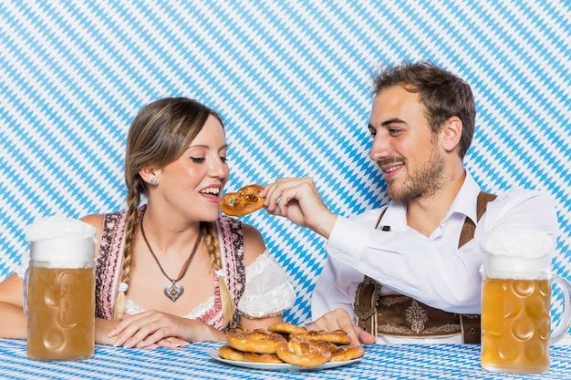Couple bavarois dégustant un bretzel allemand Photo gratuit