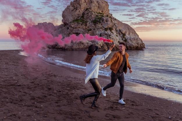 Couple avec une bombe de fumée en cours d'exécution sur le bord de mer Photo gratuit