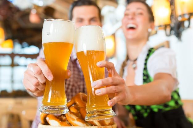 Couple buvant de la bière de blé dans un restaurant bavarois Photo Premium