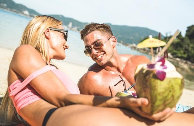 Couple buvant un cocktail à la noix de coco sur une plage tropicale Photo Premium