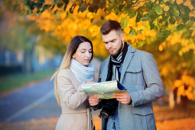 Couple avec carte et caméra dans l'allée d'automne ville. Photo Premium