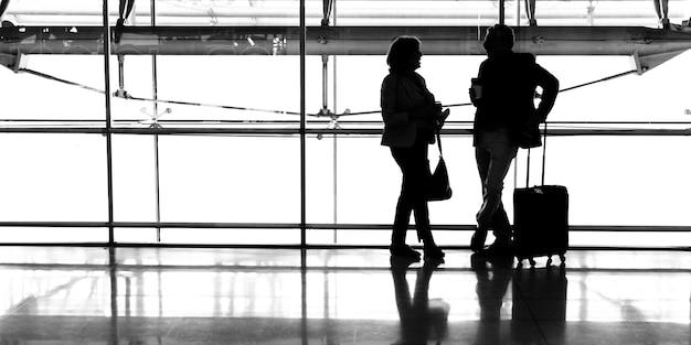 Couple caucasien parle ensemble à l'aéroport Photo gratuit