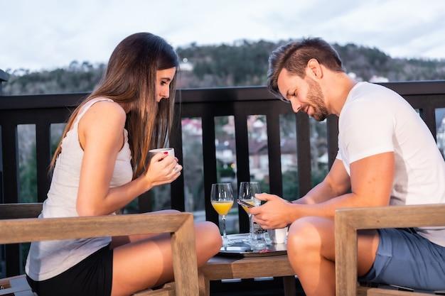 Un Couple Caucasien Prenant Son Petit Déjeuner Sur La Terrasse De L'hôtel En Pyjama. Griller Au Jus D'orange Le Matin, Mode De Vie D'un Couple Amoureux Photo Premium