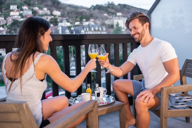 Un Couple Caucasien Prenant Son Petit Déjeuner Sur La Terrasse De L'hôtel En Pyjama. Un Jus D'orange Le Matin, Mode De Vie D'un Couple Amoureux Photo Premium