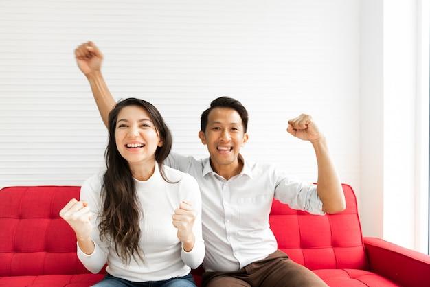 Couple célébrant sur le canapé Photo Premium