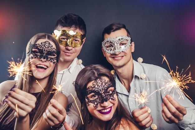 Couple célébrant le nouvel an buvant du champagne et allumant des feux de bengale lors d'une soirée masquerade Photo Premium